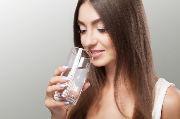 Estilo de vida saudável. retrato da jovem mulher de sorriso feliz com vidro da água fresca. cuidados de saúde. bebidas. saúde, beleza, dieta. Foto Premium