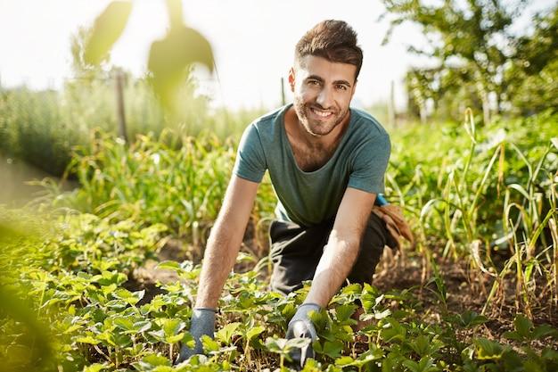 Estilo de vida saudável. vida rural. feche o retrato ao ar livre de um jovem atraente barbudo fazendeiro caucasiano sorrindo, passando a manhã no jardim perto de casa, colhendo a safra Foto gratuita