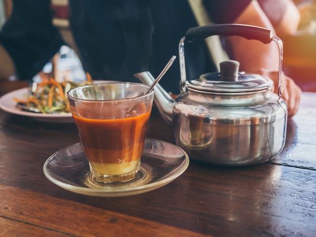 Estilo do sul tailandês do café da manhã, chá tailandês quente na chaleira do vidro e do vintage na tabela de madeira. Foto Premium