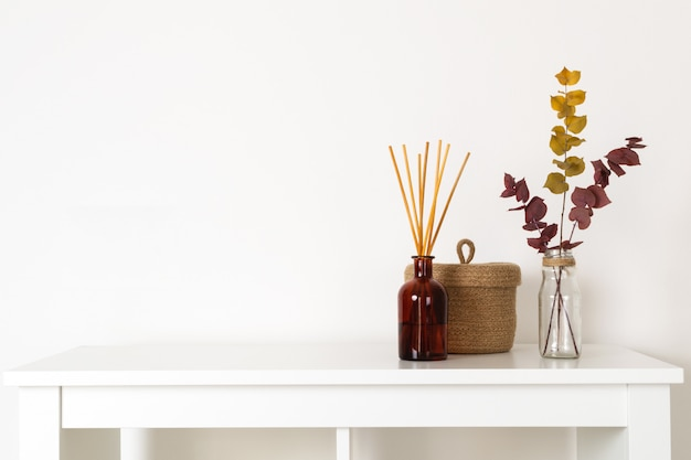 Estilo escandinavo hygge, difusor de aroma interior com varas de madeira, cesta de palha, galhos secos de eucalipto Foto Premium