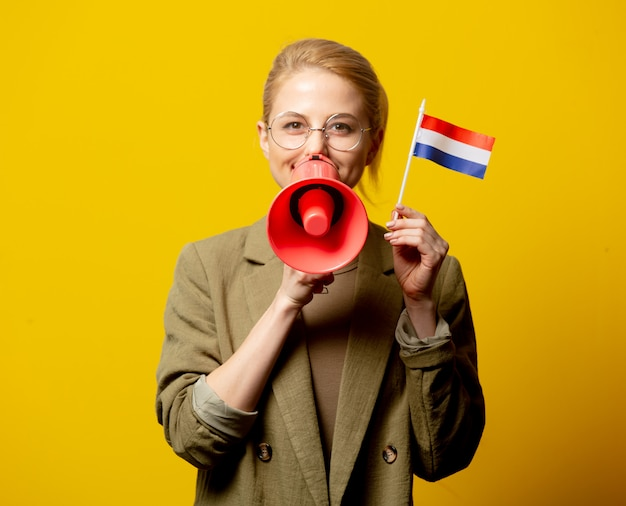 Estilo mulher loira na jaqueta com bandeira holandesa e megafone em amarelo Foto Premium