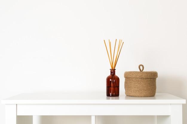 Estilo nórdico hygge escandinavo, difusor de aroma de interior para casa com varas de madeira, pequena cesta de palha, prateleira branca Foto Premium