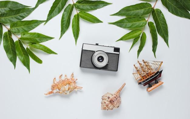 Estilo retro ainda vida de viagens. câmera de filme, conchas, folhas tropicais verdes. acessórios para viajantes em um fundo branco. vista do topo Foto Premium