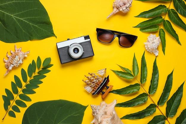 Estilo retro ainda vida de viagens. câmera de filme, óculos de sol, conchas do mar, folhas verdes tropicais. acessórios para viajantes em fundo amarelo. Foto Premium