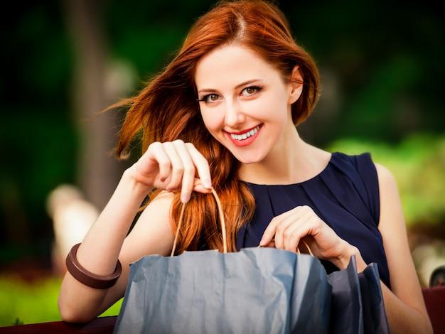 Estilo ruiva mulheres sentadas no banco com sacos de compras Foto Premium
