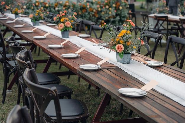 Estilo rústico de casamento, mesa de jantar de madeira com decoração de flores e utensílios de mesa Foto Premium