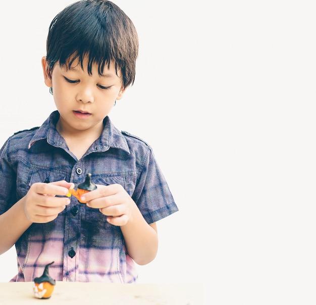 Estilo vintage de menino adorável asiático está jogando barro halloween alegremente Foto gratuita