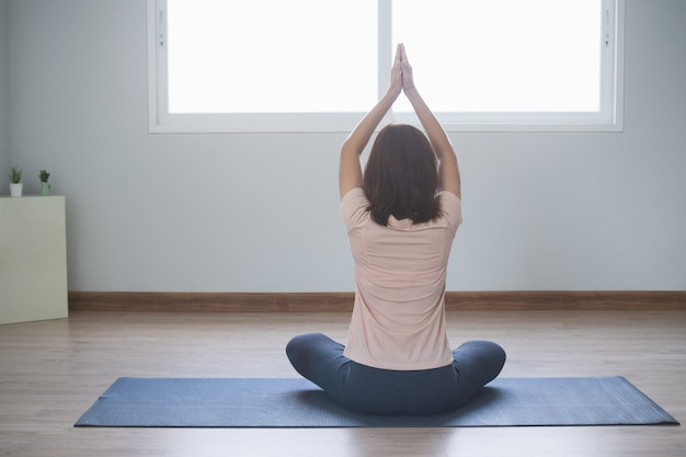 Estilos de vida de ioga e meditação. vista traseira da bela jovem praticando ioga na sala de estar em casa. Foto Premium