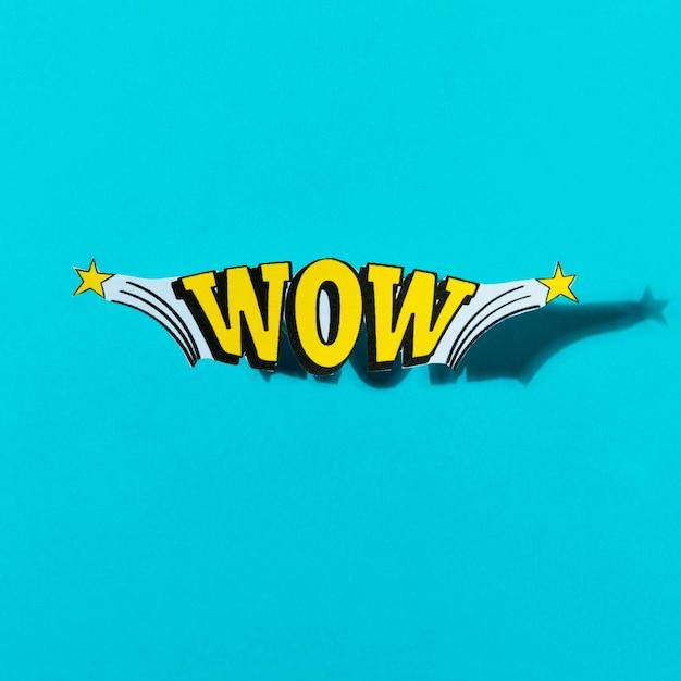 Estique o texto cômico do wow no estilo do pop art no fundo de turquesa Foto gratuita