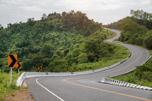 Estrada asfaltada curvada com curvas do sinal nas montanhas. Foto Premium