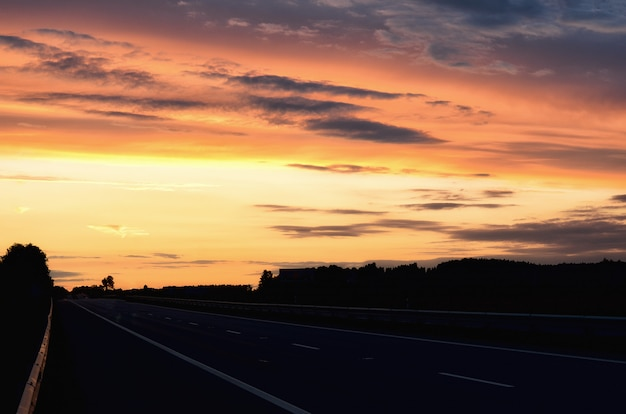 Estrada asfaltada vazia e sol que aumentam na skyline. colorido pôr do sol ao longo da estrada. design de estilo minimalista. fundo da natureza, paisagem com espaço da cópia. Foto Premium