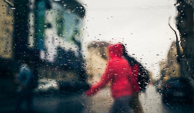 Estrada da cidade vista através da chuva cai no pára-brisa do carro Foto Premium