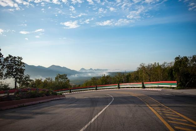 Estrada da curva que conduz um carro na estrada da montanha para baixo. nuvem bonita do céu azul da curva dramática com névoa da névoa na manhã. Foto Premium