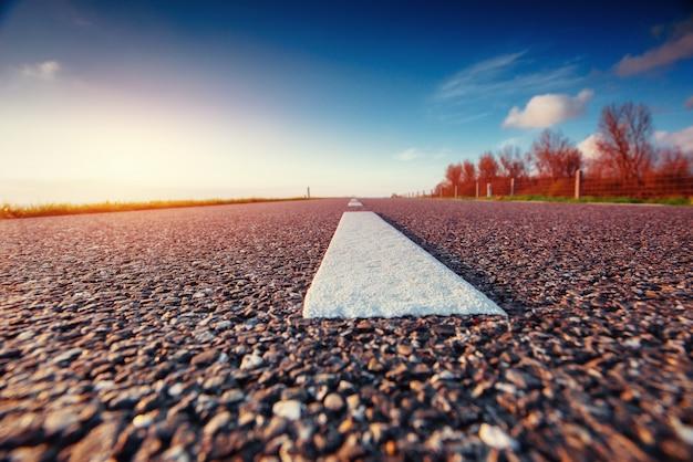 Estrada de asfalto ao longo do mar ao pôr do sol Foto Premium