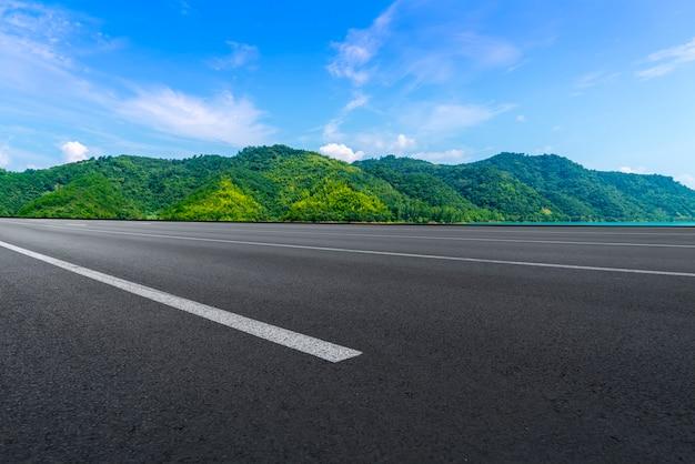 Estrada de asfalto vazia e paisagem natural sob o céu azul Foto Premium