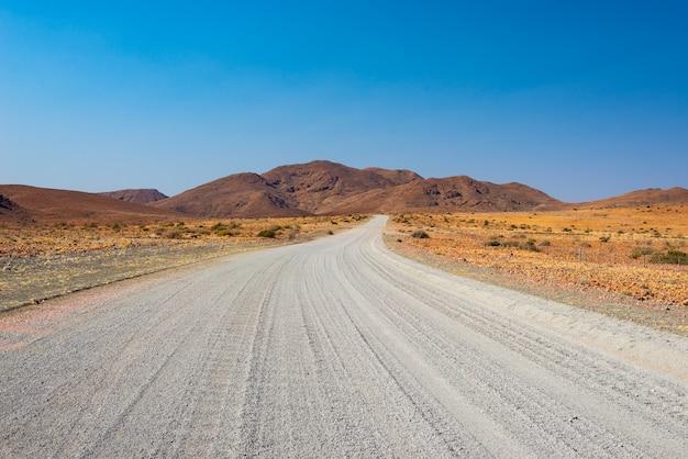 Estrada de cascalho atravessando o deserto colorido em twyfelfontein, no damaraland brandberg Foto Premium