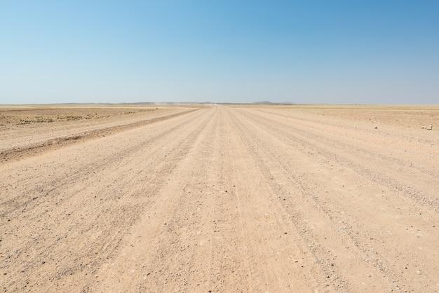 Estrada de cascalho que cruza o colorido deserto do namibe, no majestoso namib naukluft national park, o melhor destino de viagem na namíbia, áfrica. Foto Premium