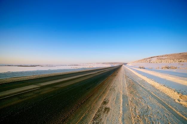 Estrada de inverno por campos nevados e florestas Foto Premium