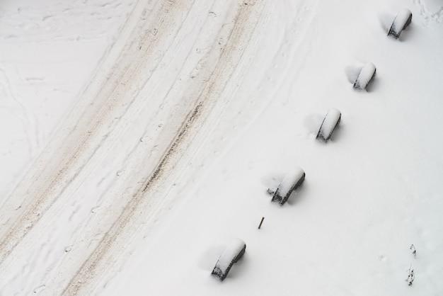 Estrada de neve. esgrima de rodas antigas. cerca de pneus. Foto Premium