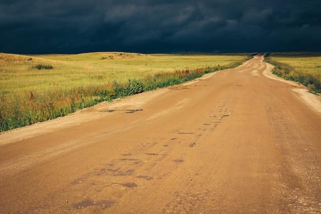 Estrada de terra à linha do horizonte sob nuvens de tempestade escuras dramáticas. Foto Premium