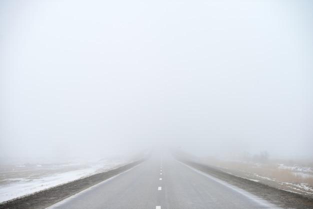 Estrada desaparecendo no nevoeiro Foto Premium