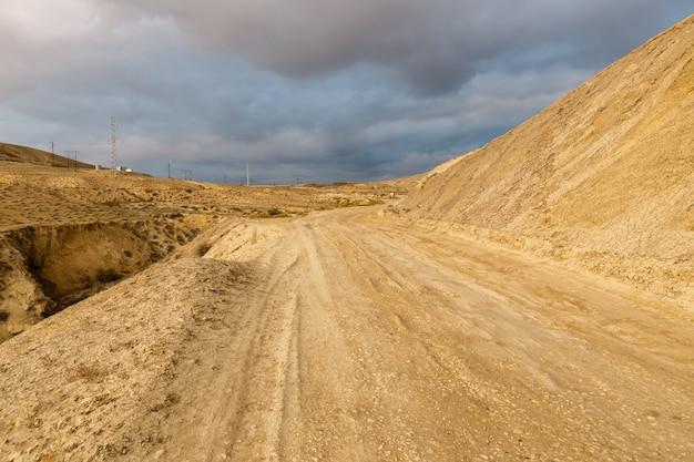 Estrada para enlamear vulcões de gobustan perto de baku, azerbaijão. estrada e céu tempestuoso Foto Premium