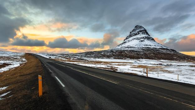 Estrada para kirkjufell sob o céu nublado ao entardecer Foto Premium