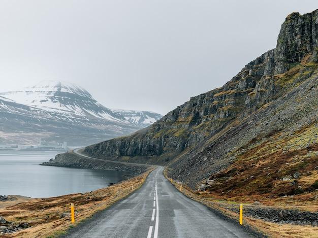 Estrada sinuosa cercada pelo mar e rochas cobertas por vegetação e neve sob um céu nublado Foto gratuita