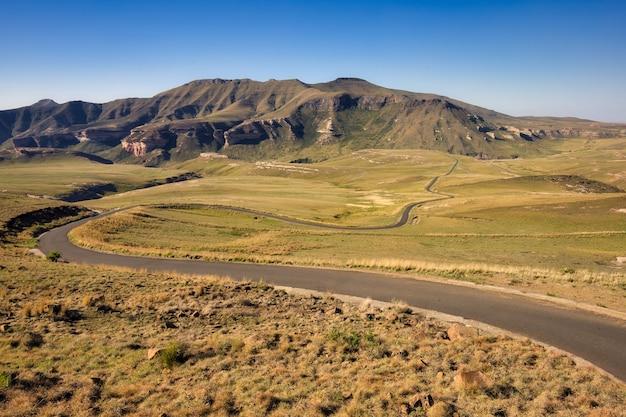 Estrada sinuosa no meio de campos gramados com montanhas à distância na província do cabo oriental Foto gratuita