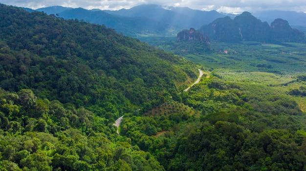 Estrada sinuosa no vale da montanha ao pôr do sol. vista aérea da estrada asfaltada em tailândia. vista superior da estrada, montanhas, floresta verde, céu azul e luz solar Foto Premium