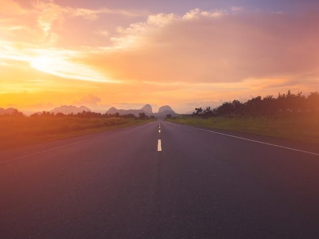 Estrada velha contra montanhas e um céu nublado durante o pôr do sol. Foto Premium