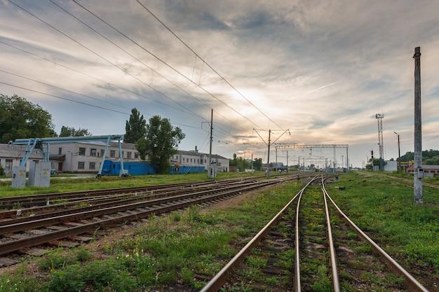 Estradas de ferro contra o céu bonito no por do sol. paisagem industrial com entroncamento ferroviário. industria pesada Foto Premium