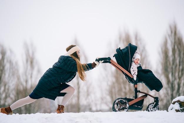 Estranha bizzare linda jovem mãe empurrando o carrinho de bebê com sua filha sentada nele através de nevascas no inverno. dificuldades na maternidade. Foto Premium