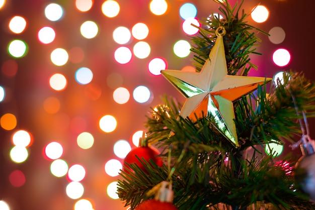 Estrela de decoração de natal e bolas penduradas em galhos de pinheiro árvore de natal Foto Premium