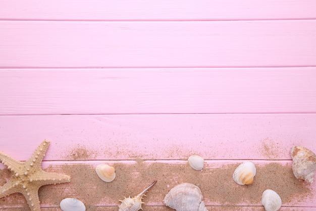 Estrela do mar e conchas do mar com areia em madeira cor-de-rosa. conceito de verão Foto Premium