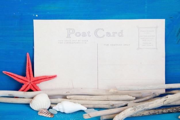 Estrela do mar, madeiras resistidas e conchas na vista superior da parede de madeira azul com espaço de cópia em papel Foto Premium