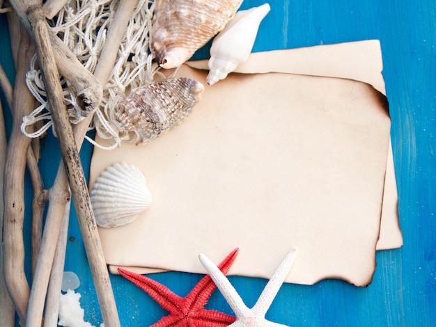 Estrela do mar, madeiras resistidas, rede e conchas na vista superior da parede de madeira azul com espaço de cópia em papel Foto Premium
