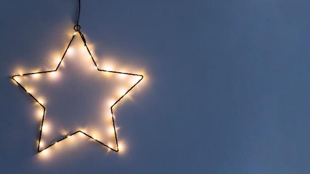 Estrela feita de guirlanda ardente na parede Foto gratuita