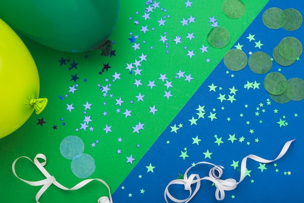 Estrelas de confetes e balões em fundo colorido Foto gratuita