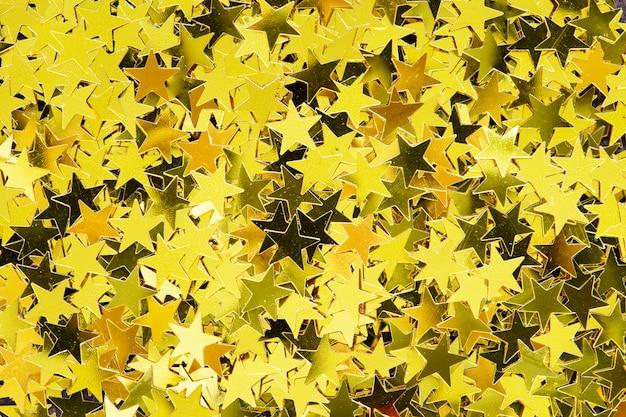 Estrelas douradas brilhantes brilham fundo festivo Foto gratuita