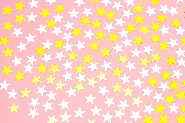 Estrelas douradas de confete sobre um fundo branco, vista superior Foto Premium