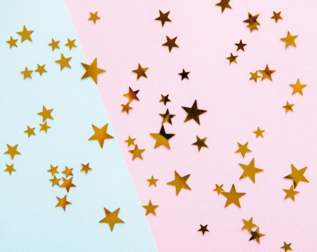 Estrelas douradas sobre fundo rosa Foto Premium
