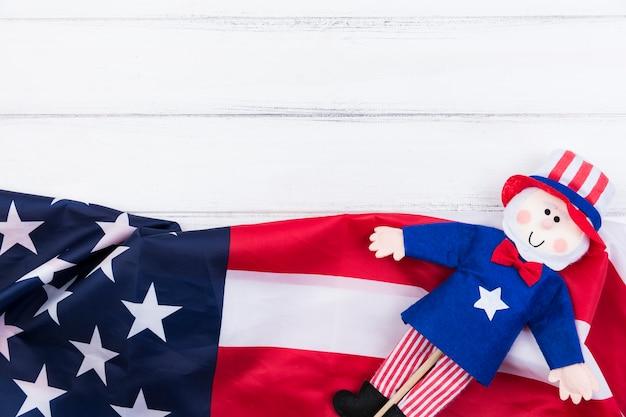 Estrelas e listras da bandeira americana e boneca azul-vermelho na superfície branca Foto gratuita
