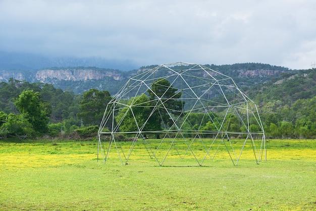Estrutura metálica na grama verde e céu azul. Foto gratuita