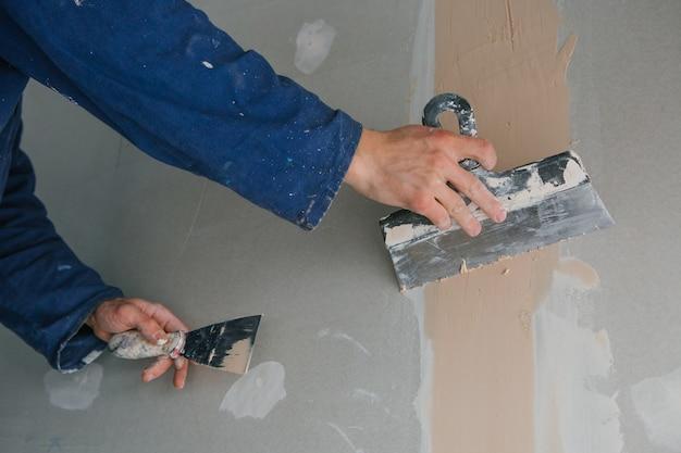 Estucador homem trabalha emplastrando duas picaretas em gesso cartonado em uniforme azul Foto gratuita