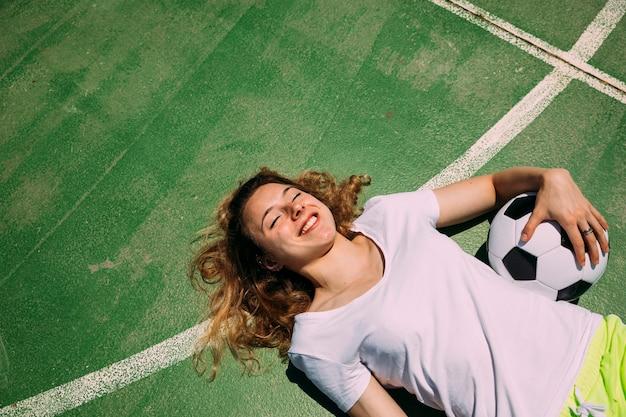 Estudante adolescente alegre deitado no campo de futebol Foto gratuita