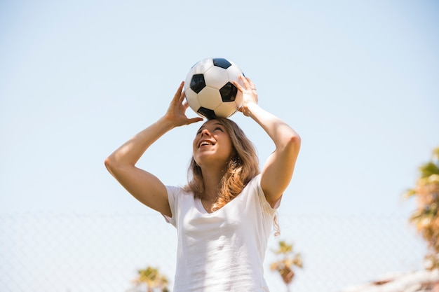 Estudante adolescente alegre segurando uma bola de futebol na cabeça Foto gratuita