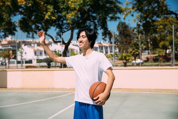 Estudante adolescente asiática mostrando o gesto de saudação no tribunal Foto gratuita