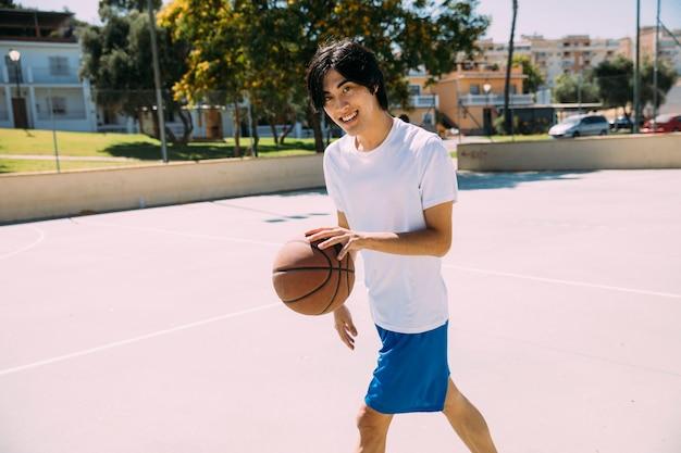 Estudante adolescente asiático de sorriso que joga o basquetebol Foto gratuita
