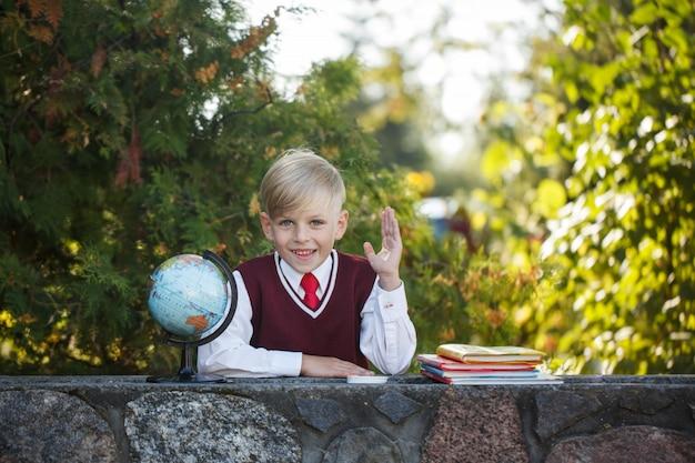Estudante adorável com livros e globo no ar livre. educação para crianças. volta ao conceito de escola. Foto Premium
